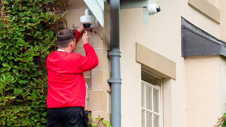 engineer on ladder fitting a cctv